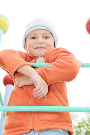 Smiling boy in orange jacket on climbing staircase outdoors photo