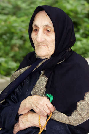 looking sideways: Elderly woman with beads looking sideways sitting outdoors closeup photo Stock Photo