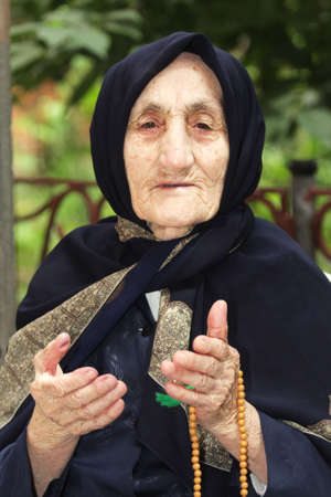 gesticulating: Elderly woman with beads gesticulating while talking outdoors closeup photo