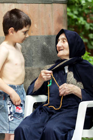Little boy listens to old granny in summer backyard Stock Photo - 7757202