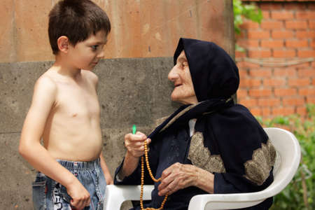 Little kid listens to old granny in summer backyard Stock Photo - 7757207
