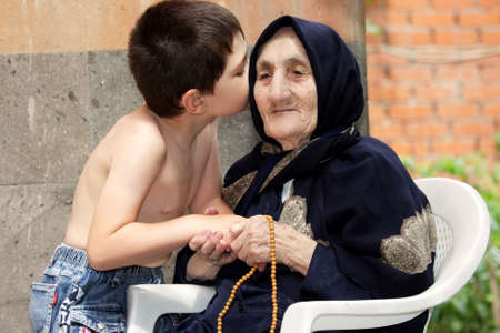 Little kid whispers to old granny in summer backyard sharing secrets  Stock Photo - 7757206