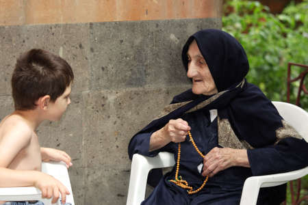 Little kid chatting with old granny in summer backyard both sitting in chairs Stock Photo - 7757204