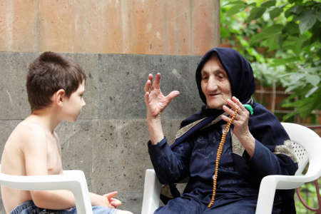 Granny telling tales to grandson while sitting in summer backyard Stock Photo - 7757209