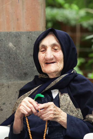 Smiling elderly woman with beads looking sideways outdoors Stock Photo - 7757200