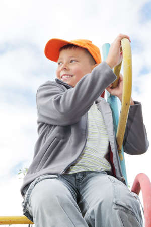looking sideways: Smiling boy sitting on climbing staircase looking sideways outdoors
