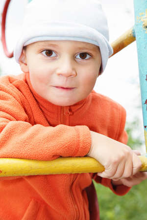 Funny kid in orange jacket on climbing staircase outdoors photo