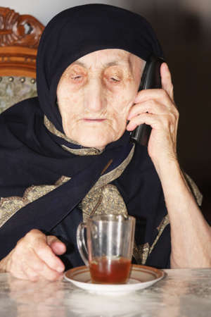 Elderly woman sitting at table with cup of tea and phone Stock Photo - 7757249