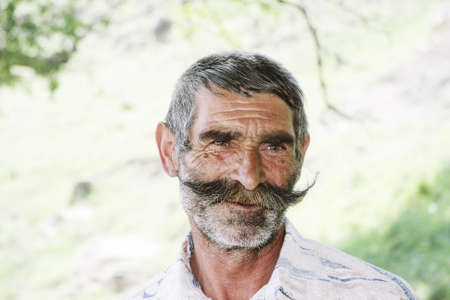 Serene elderly man with great moustaches closeup outdoors photo photo