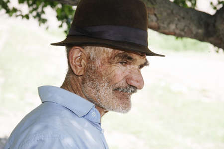 Thoughtful elderly man in hat profile view outdoors Stock Photo - 7757283