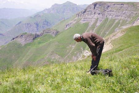 Senior man bowing while praying in mountains sideview photo Stock Photo - 7757288