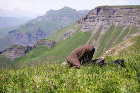 Senior man making low bow while praying in mountains Stock Photo - 7757289