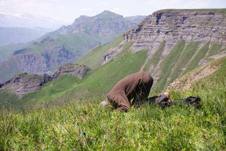 Senior man making low bow while praying in mountains Stock Photo - 7757289
