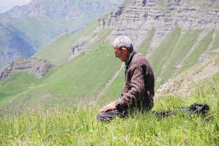 Senior man kneeling while praying in summer mountains photo