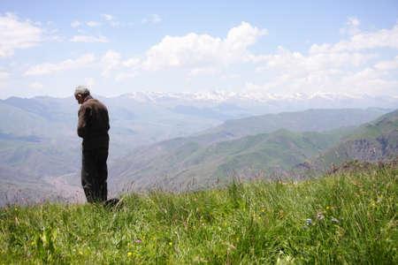 Praying senior man in summer mountains rear view