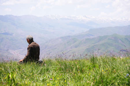 Senior man kneeling while praying in mountains rear view