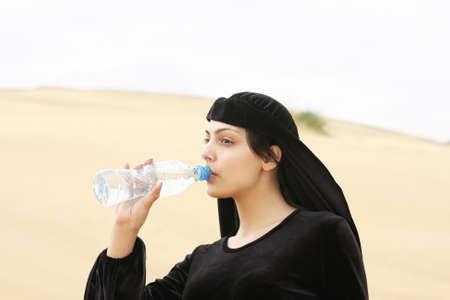 looking sideways: Young woman drinking water from bottle looking sideways