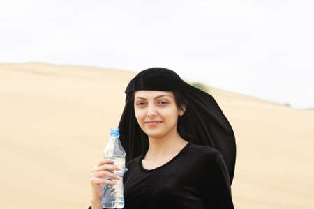 Smiling woman with water bottle standing on sand hill in desert Stock Photo - 7757295
