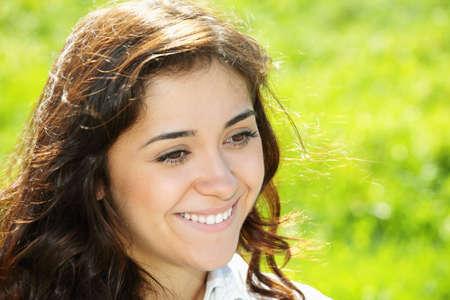 looking sideways: Young smiling brunette looking sideways head and shoulders outdoor portrait