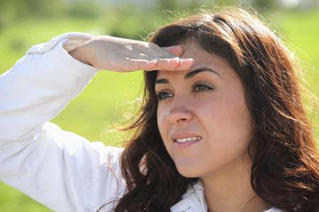 looking sideways: Young brunette woman looking sideways from under hand peak