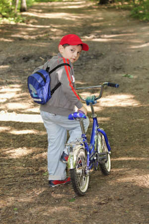 glancing: Little boy with bicycle glancing back on forest path