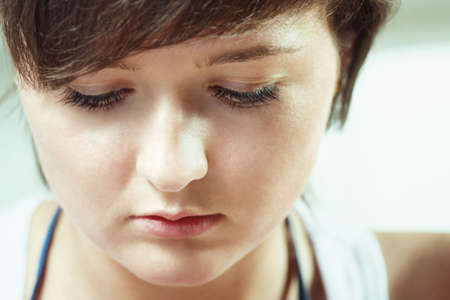 Young brunette woman looking down closeup photo