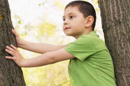 looking sideways: Little boy sitting between trees looking sideways Stock Photo