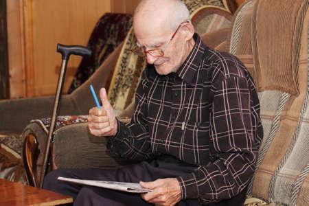Senior man gesturing thumb up while reading newspaper indoors