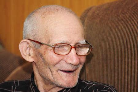 looking sideways: Smiling senior man in eyeglasses looking sideways indoor portrait Stock Photo