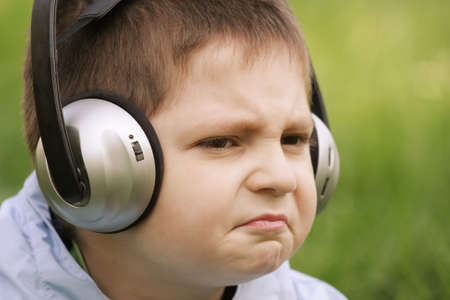 sceptic: Closeup portrait of sceptic little boy in headphones looking sideways