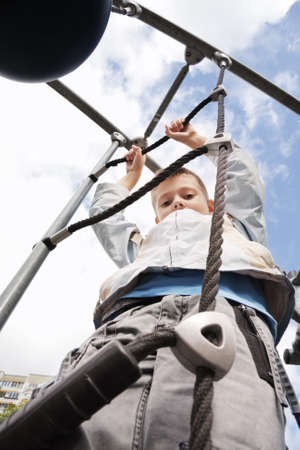 Boy in blue jacket on top of rope ladder against clouds on sky photo