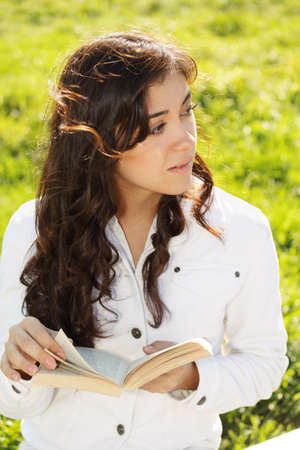 looking sideways: Young brunette woman in white with book looking sideways