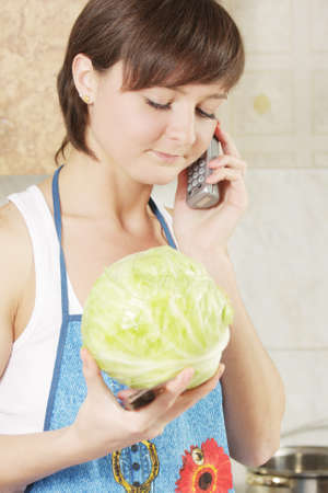 interrupted: Young brunette houswife with cabbage interrupted by phone Stock Photo