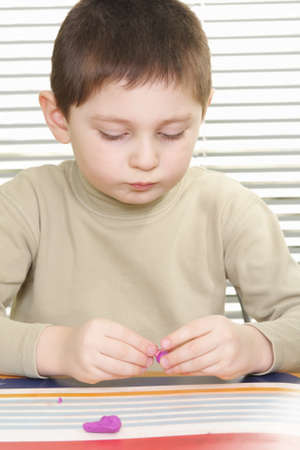 sculp: Little brunette boy modelling with plasticine sitting at desk