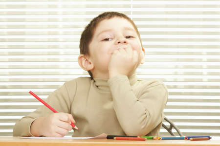 contented: Contented little boy with red crayon sitting at desk