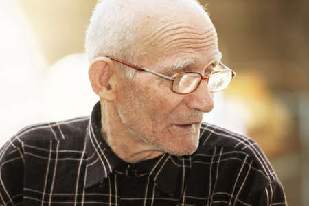 Senior man in eyeglasses looking sideways outdoor portrait Stock Photo - 8022423