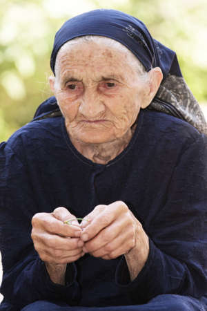 Serious elderly woman recollecting while sitting at backyard Stock Photo - 8022672