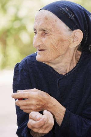 Closeup portrait of elderly woman in blue looking sideways Stock Photo - 8022673