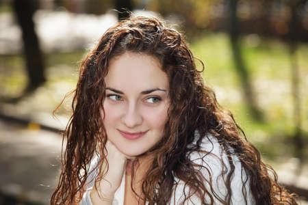 looking sideways: Cute young curly woman outdoors looking sideways