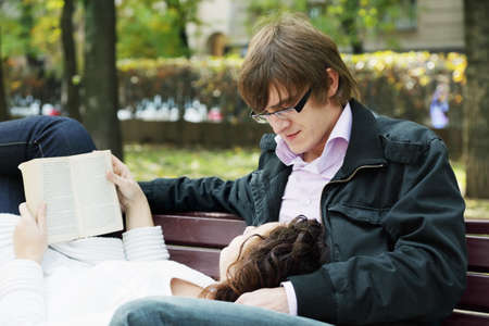 Relaxed couple with book on bench in autumn park photo