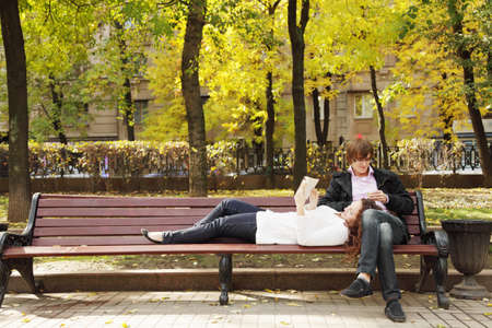 Couple spending time in autumn park on brown bench photo