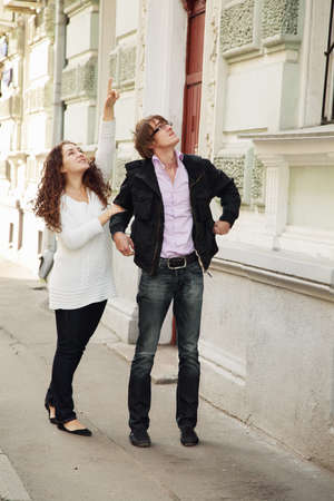 sightseeng: Young couple in casual clothes walking by city looking up Stock Photo