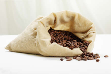 Scattered coffee beans scattered by white tabletop from bag Stock Photo