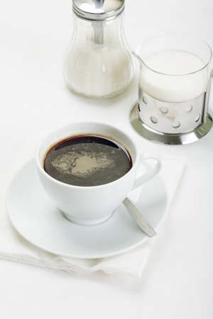 White cup of espresso coffee with sugar and milk on tabletop photo