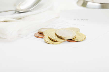 Several coins laying down on receipt selective focus photo