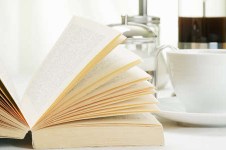 Book and coffee with various food on white tablecloth Stock Photo