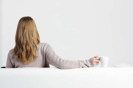 Blonde woman in gray sweater sitting on sofa in front of empty wall photo