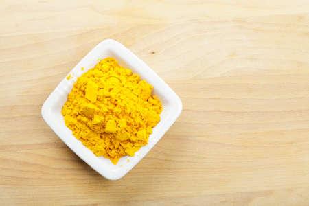 Saffron spice in white dish on wooden board above view photo