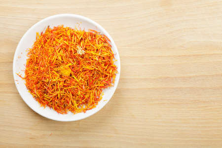 Saffron leaves spice in white saucer on wooden plank above view photo