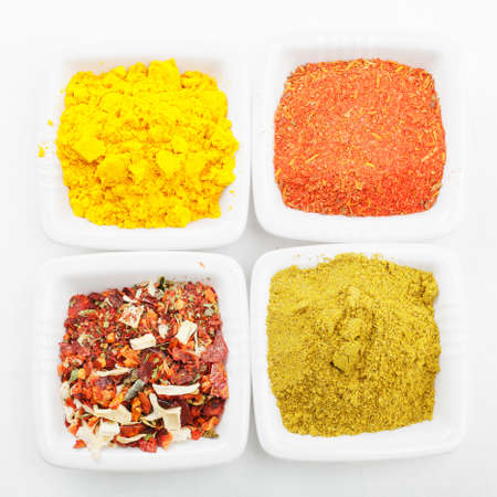 Various spices in white dishes on tablecloth above view Stock Photo - 8176617